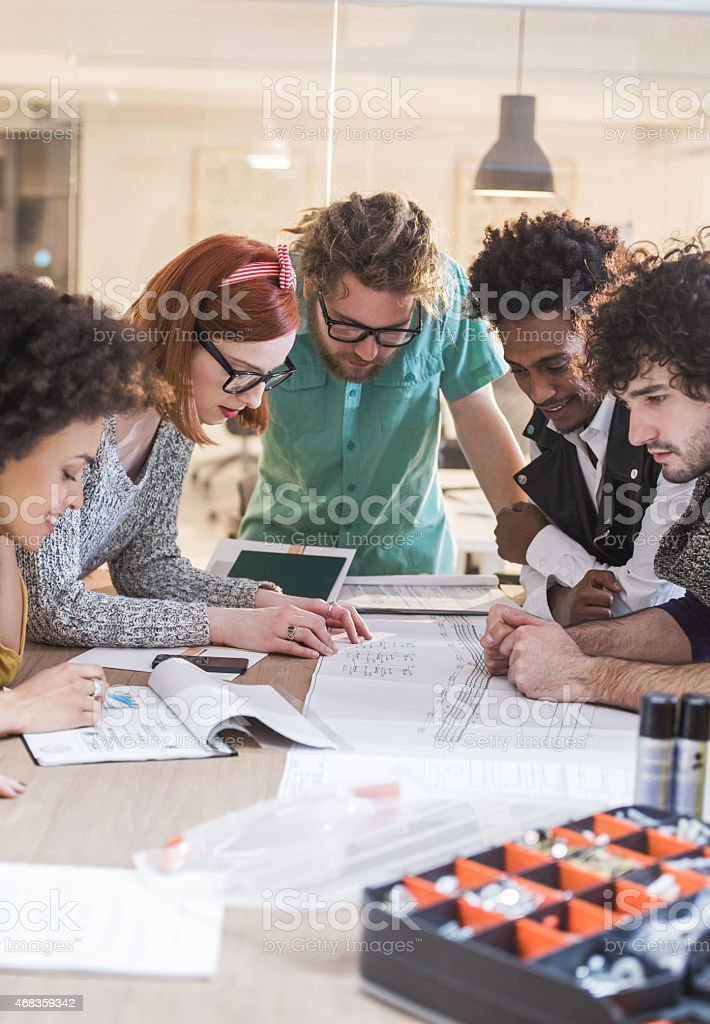 Young architects working on blue prints in the office. royalty-free stock photo