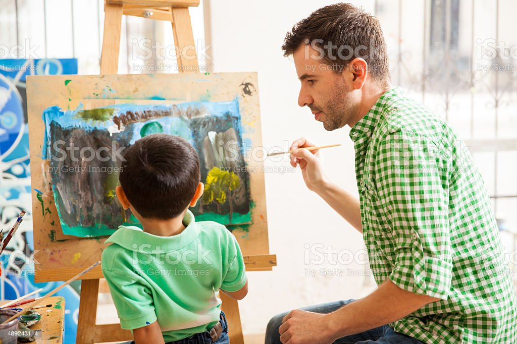 Young art teacher doing his job stock photo