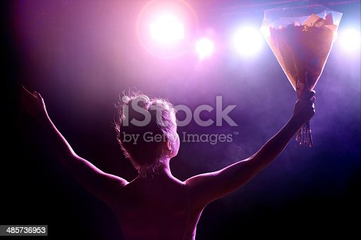 Horizontal composition color photography of young woman artist (singer or classical dancer) receives a bouquet of flowers on stage at the end of the spectacle as a thank you, and saluting the public. Rear view from backstage with spotlight in camera creating lens flare.