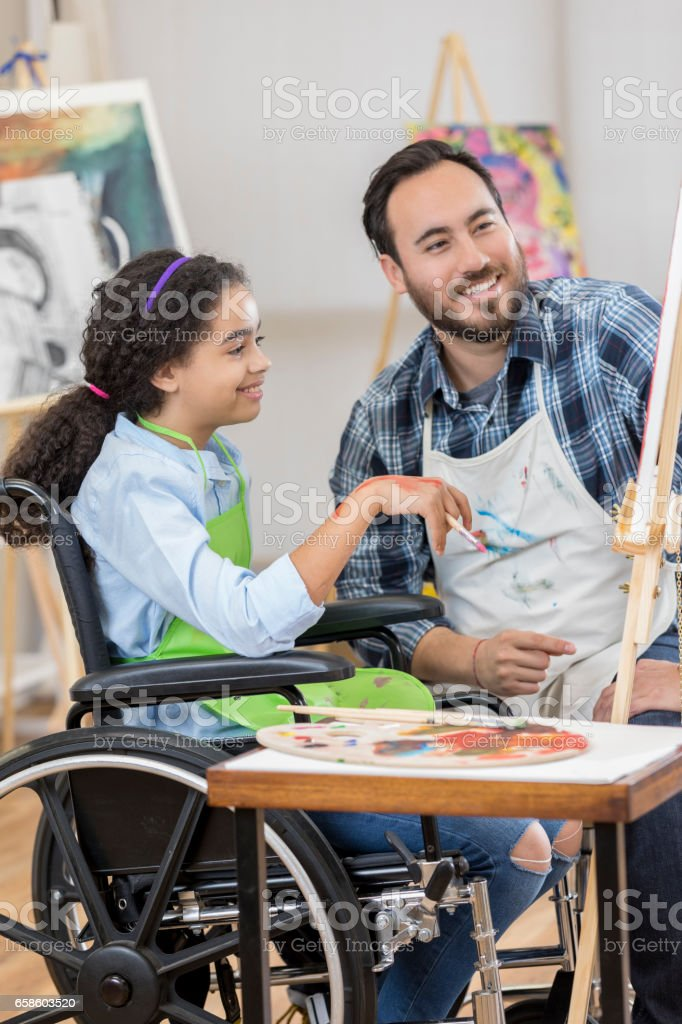 Young artist in wheelchair takes art lesson stock photo