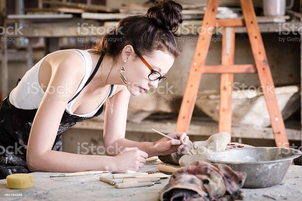 young artist moulding raw clay in art studio stock photo