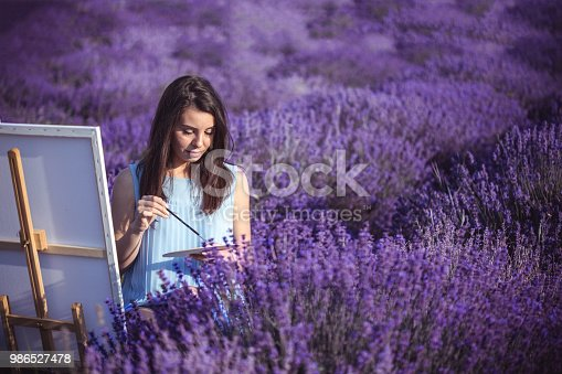 671393252 istock photo Young artist painting an floral landscape 986527478