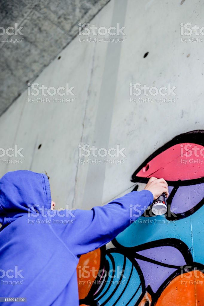 Young Artist Painting Concrete Wall With Spray Paint Stock