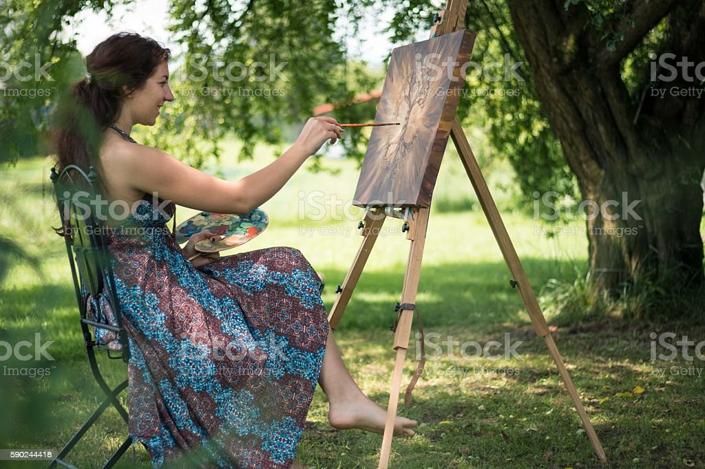 Young artist painting outside in nature - Photo