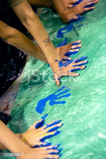 istock Young artist using blue fingerprint to make a handprint 157287733
