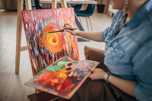 One young woman, female painter, painting in her studio.