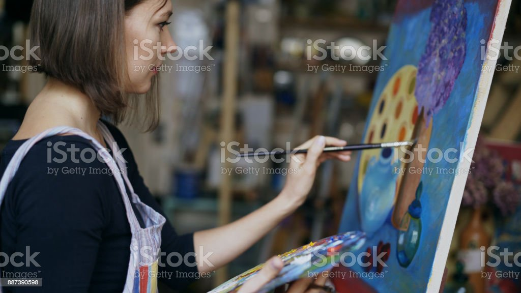 Young artist woman painting still life picture on canvas in art-school stock photo