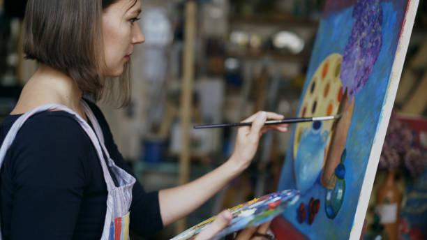 年輕演出者婦女繪畫靜物畫在帆布在藝術學校 - 畫畫 動態活動 個照片及圖片檔