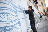 young artists draw murals on the wall