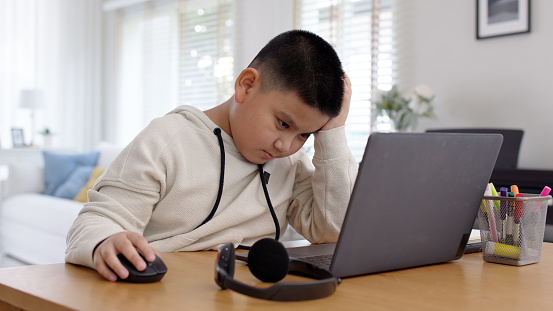 Young asia boy kid sit on desk look at computer notebook feeling bored tired and sleepy in remote learning loss online problem at home distant e-learning primary school class room challenge concept.