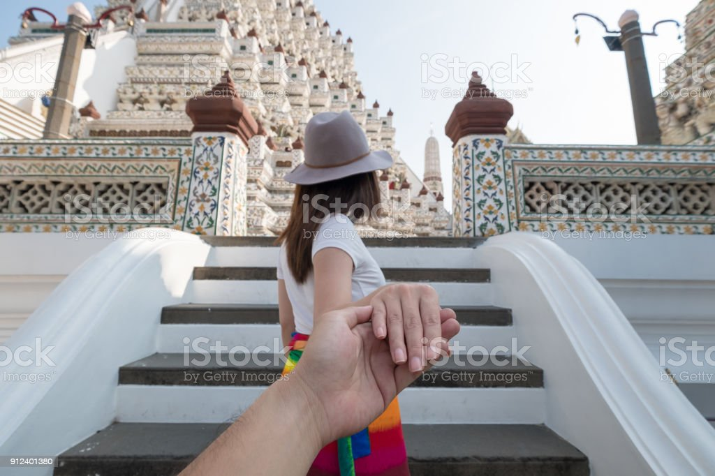 Young asia couple traveling at Wat arun temple in Bangkok, Woman holding man hand to lead the journey concept stock photo