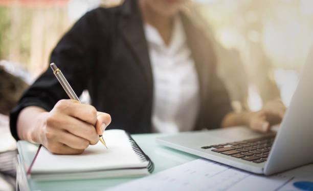 giovane studente asia studio nella biblioteca pubblica, lei prendendo nota su notebook e utilizzando laptop - internet foto e immagini stock