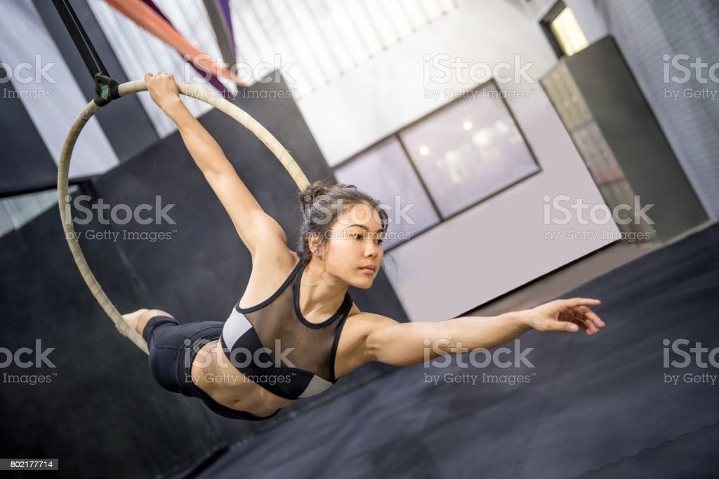 young asian acrobatic woman doing her gymnastics performance on aerial hoop stock photo