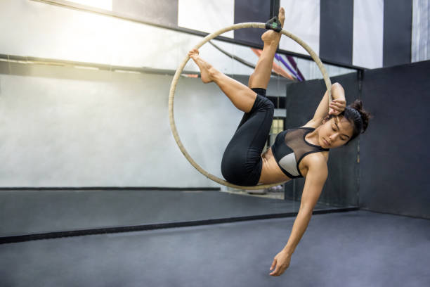 young asian acrobatic woman doing her gymnastics performance on aerial hoop - equilibrista foto e immagini stock