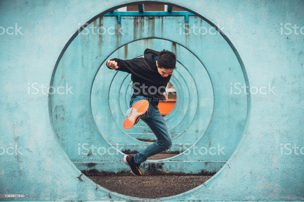 Young Asian active man in action of jumping and kicking, circle...