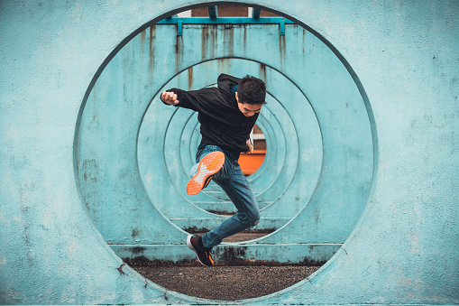 istock Young Asian active man in action of jumping and kicking, circle looping wall background. Extreme sport activity, parkour outdoor free running, or healthy lifestyle concept 1083827840