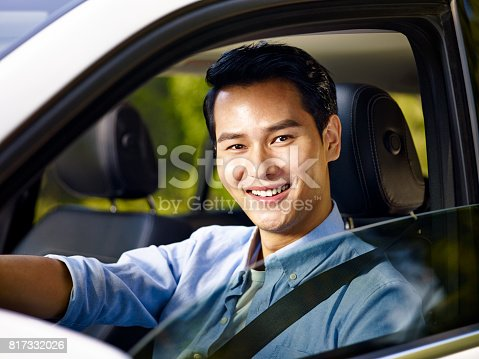 istock young asian adult driving a car wearing seat belt 817332026