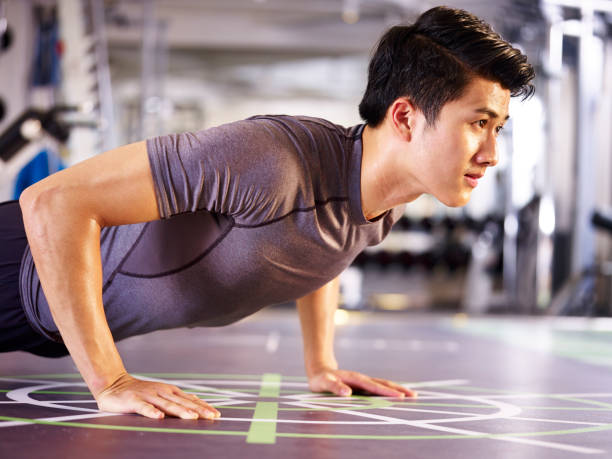 young asian adult exercising in gym - push up stock photos and pictures