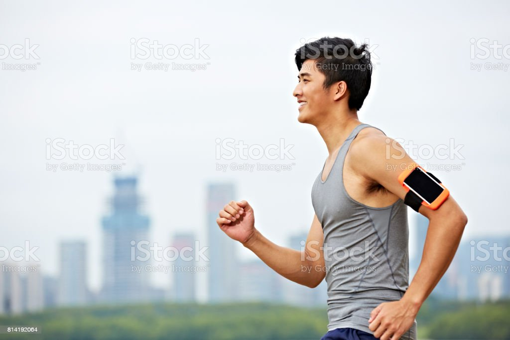 young asian adult running in park stock photo