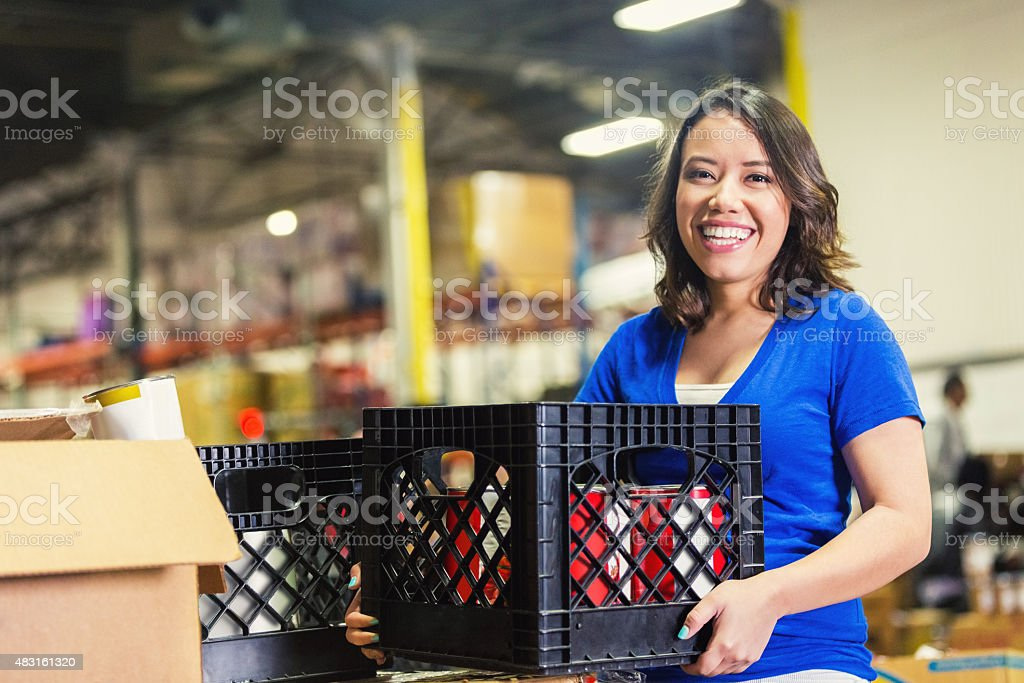 Young Asian American volunteer working in food bank warehouse stock photo