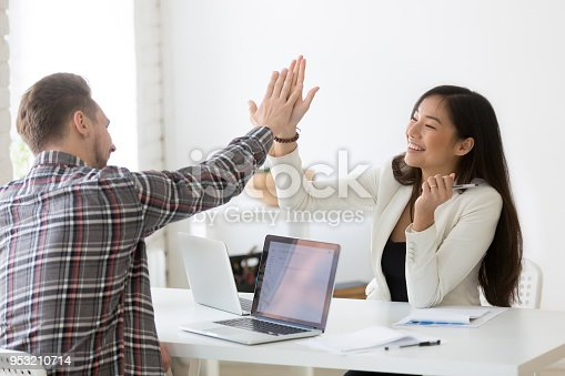 istock Young asian and caucasian partners giving high-five celebrating goal achievement 953210714