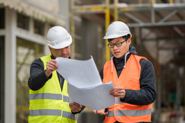 Young Asian apprentice at work on construction site with senior engineer. Outdoors stock photo