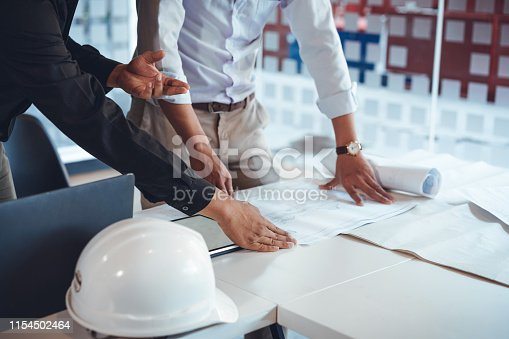 832105172 istock photo Young asian architect colleagues discussing about construction plans on blueprint and tablet at construction site office. Architect using technology concept. 1154502464