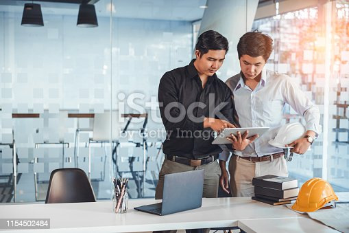 832105172 istock photo Young asian architect colleagues discussing about construction plans on tablet at construction site office. Architect using technology concept. 1154502484