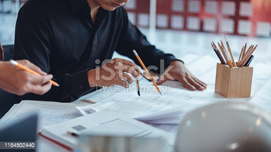 832105172 istock photo Young asian architect colleagues sketching and discussing about construction plans on blueprint at construction site office. 1154502440