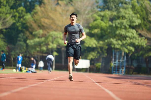 アジアの若い選手はトレーニング ランニング トラックが ストックフォト