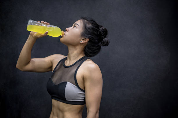 Young Asian athlete woman drinking sport drink or energy drink after exercise stock photo
