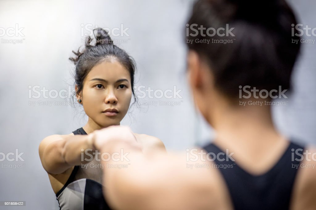 young asian athletic women in sportswear punching and looking herself in the mirror stock photo