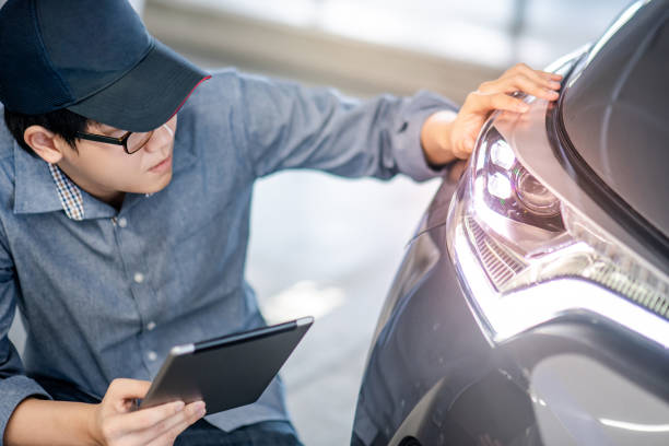 Young Asian auto mechanic holding digital tablet checking headlight in auto service garage. Mechanical maintenance engineer working in automotive industry. Automobile servicing and repair concept Young Asian auto mechanic holding digital tablet checking headlight in auto service garage. Mechanical maintenance engineer working in automotive industry. Automobile servicing and repair concept headlight stock pictures, royalty-free photos & images