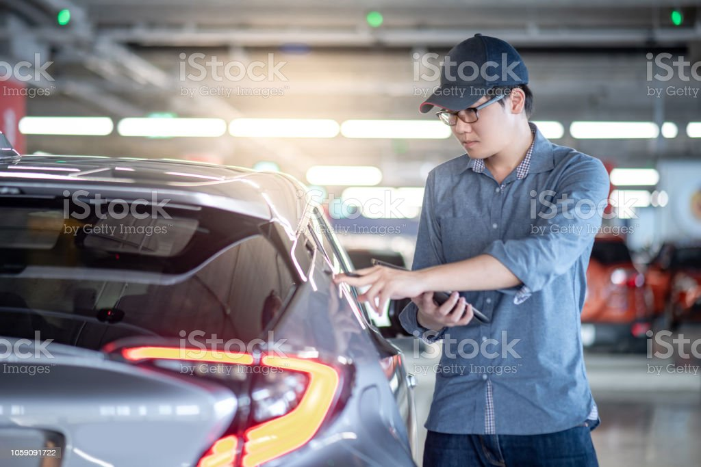 Young Asian auto mechanic holding digital tablet checking tail light...