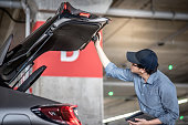 Young Asian auto mechanic holding digital tablet checking tailgate in auto service garage. Mechanical maintenance engineer working in automotive industry. Automobile servicing and repair concept