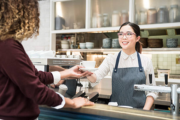 young asian barista serving coffee to female customer in cafe - barista stock photos and pictures