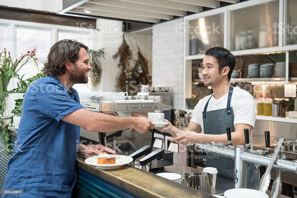 Young Asian barista serving mid adult man coffee in cafe stock photo