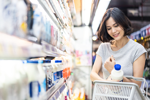 Young Asian beautiful woman holding grocery basket walking in supermarket. She is choosing daily milk product picking up from shelf. Seen from side while she looking at products. Shopping concept.