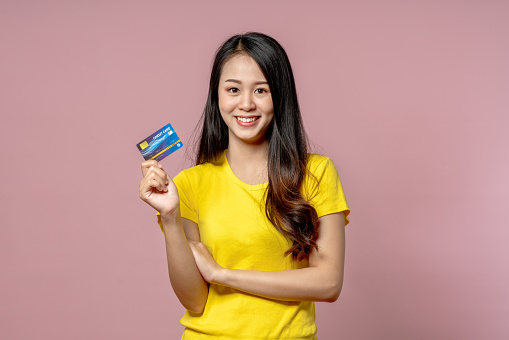 Young asian beautiful woman in yellow shirt smiling and showing credit card in hand feeling trust and confident for making payment with studio shot on pink background.