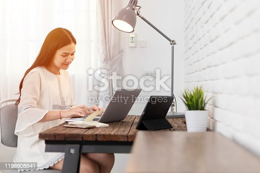 Young asian beautiful woman using laptop at home.  Portrait of young woman smiling and looking at laptop screen .
