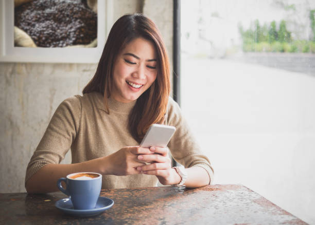 young asian beautiful woman using smart phone for business, online shopping, transfer money, financial, internet banking. in coffee shop cafe over blurred background. - dispositivo informatico portatile foto e immagini stock