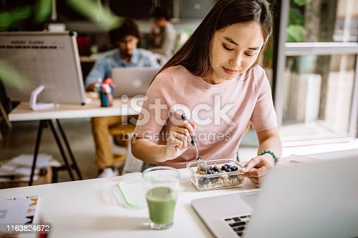 Young Asian blogger having vegetarian breakfast at work