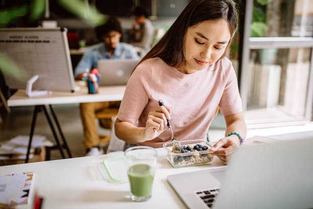 Young Asian blogger having vegetarian breakfast at work stock photo