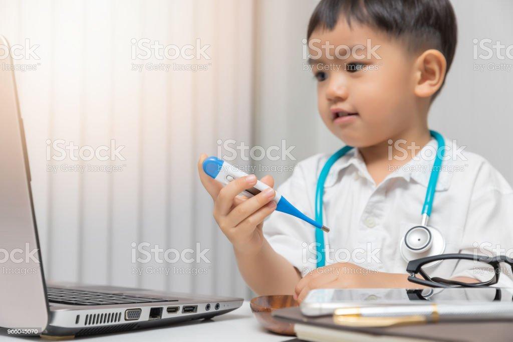 Unga asiatiska pojke spelar läkare och hålla en termometer. - Royaltyfri Akademikeryrke Bildbanksbilder