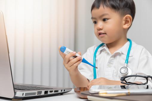 Unga Asiatiska Pojke Spelar Läkare Och Hålla En Termometer-foton och fler bilder på Akademikeryrke