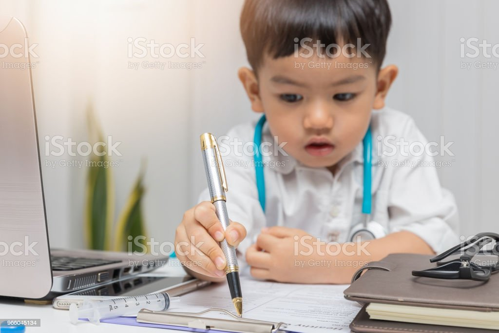 Young asian boy playing doctor and writing on diagnostic chart. - Royalty-free Anthropomorphic Smiley Face Stock Photo