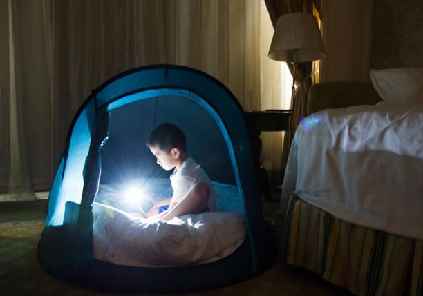 asiatische junge spielen im zelt - deckenleuchte kinderzimmer stock-fotos und bilder