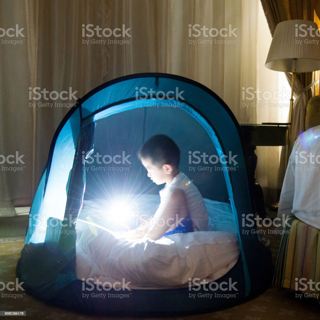 Young asian boy playing in tent stock photo