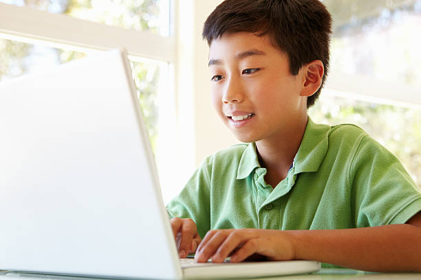 A young Asian boy using his white laptop stock photo