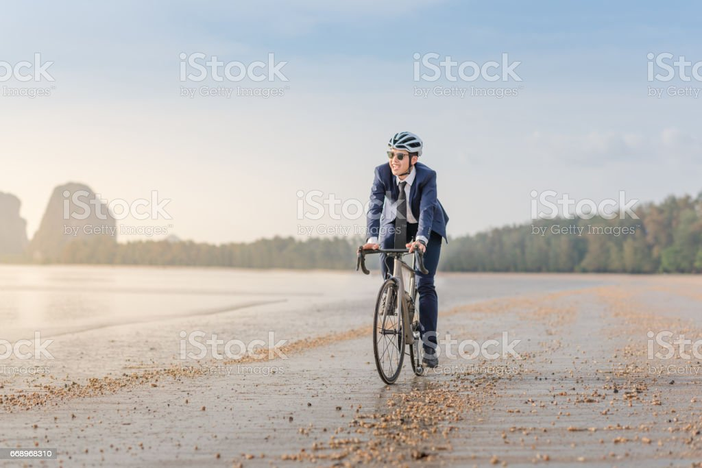 Young asian business man ride  bicycle relaxing  the beach at the sunset foto stock royalty-free